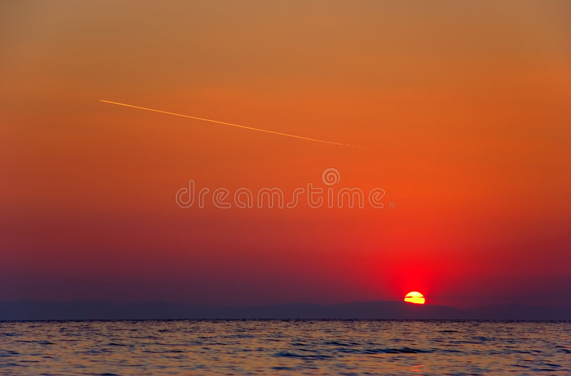 Nascer do sol com um vôo plano no céu fotografia de stock royalty free