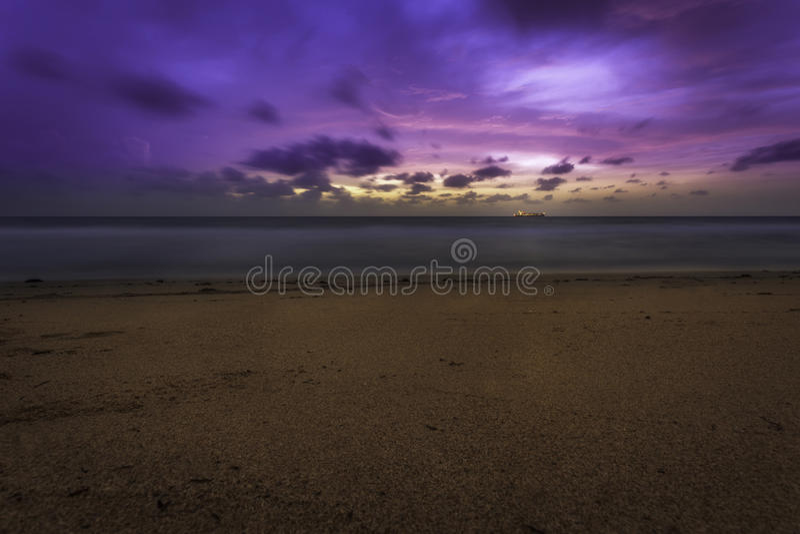 Nascer do sol cor-de-rosa e roxo da praia com o navio no horizonte foto de stock royalty free