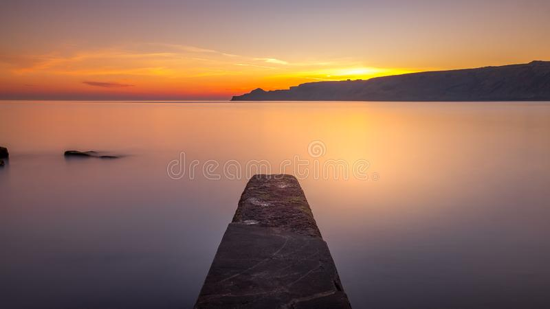 Nascer do sol da costa de North Yorkshire na baía de Runswick imagem de stock