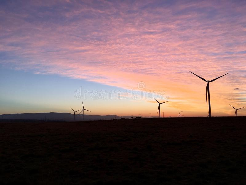 Nascer do sol da manhã das turbinas eólicas foto de stock