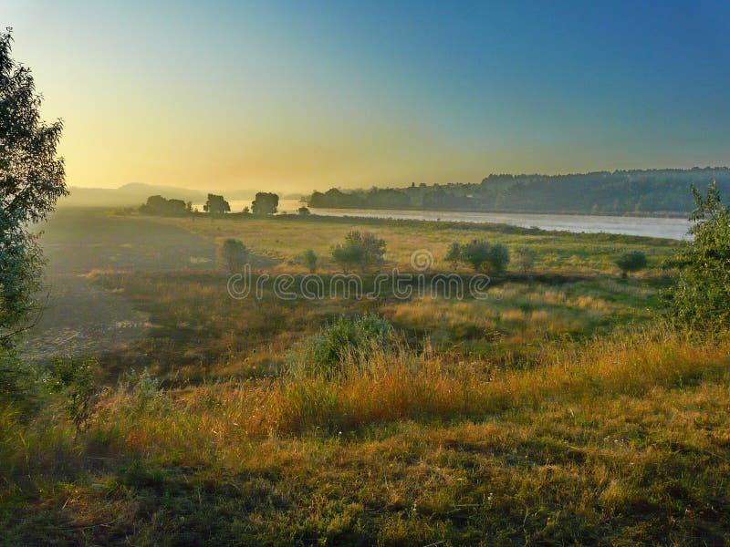 Nascer do sol da manhã sobre um grande campo bonito, umas árvores verdes e um a imagens de stock