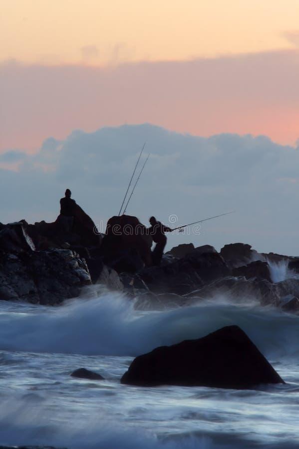 Nascer do sol da pesca da rocha imagens de stock