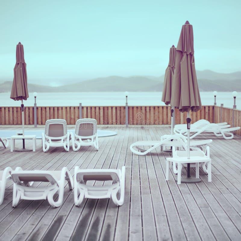 Nascer do sol de madeira do céu da associação do hotel do guarda-chuva do vadio do sol do recurso do oceano do mar da praia da pl foto de stock