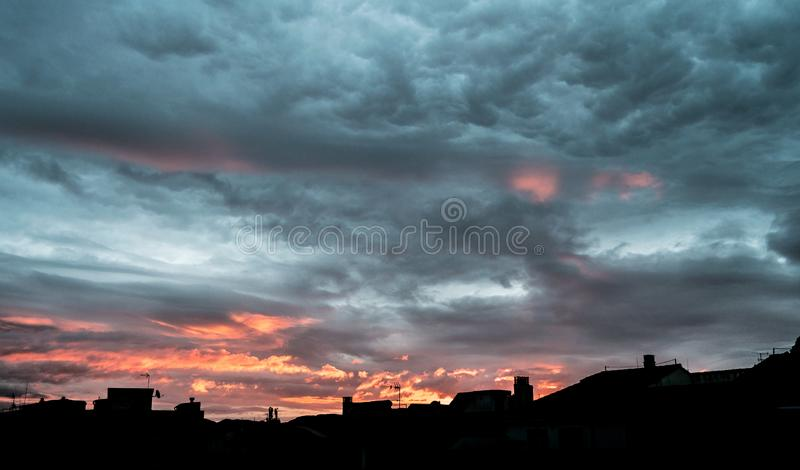 Nascer do sol de surpresa do céu nebuloso Escuro - nuvens dramáticas assustadores da tempestade alaranjada no nascer do sol bonit fotos de stock royalty free