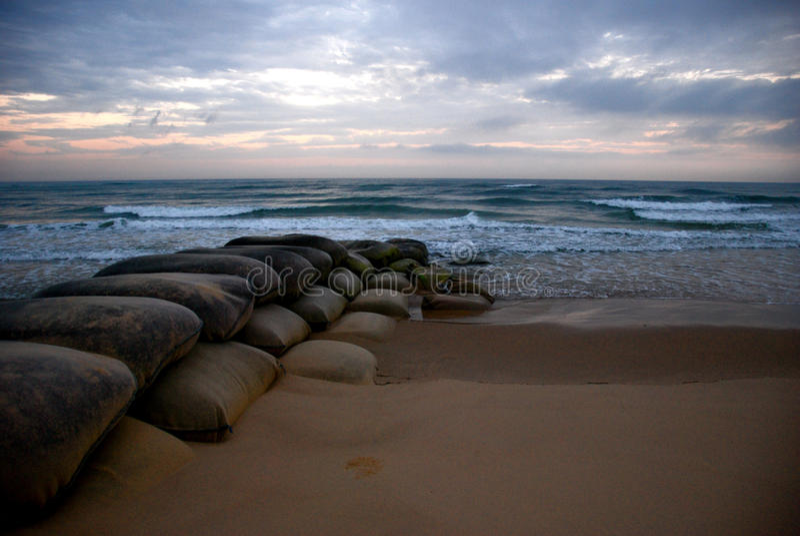 Nascer do sol do oceano com sacos de areia imagens de stock royalty free