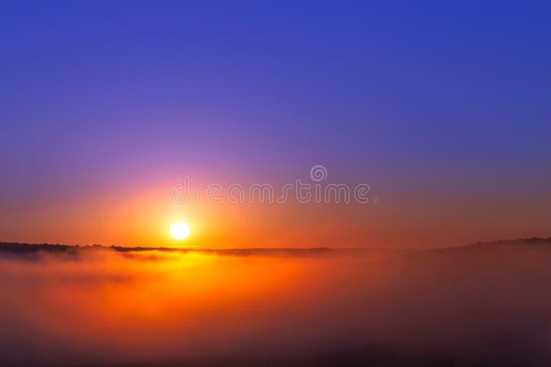 nascer do sol Dourado-azul do verão sobre a névoa sem as nuvens na composição minimalistic foto de stock royalty free