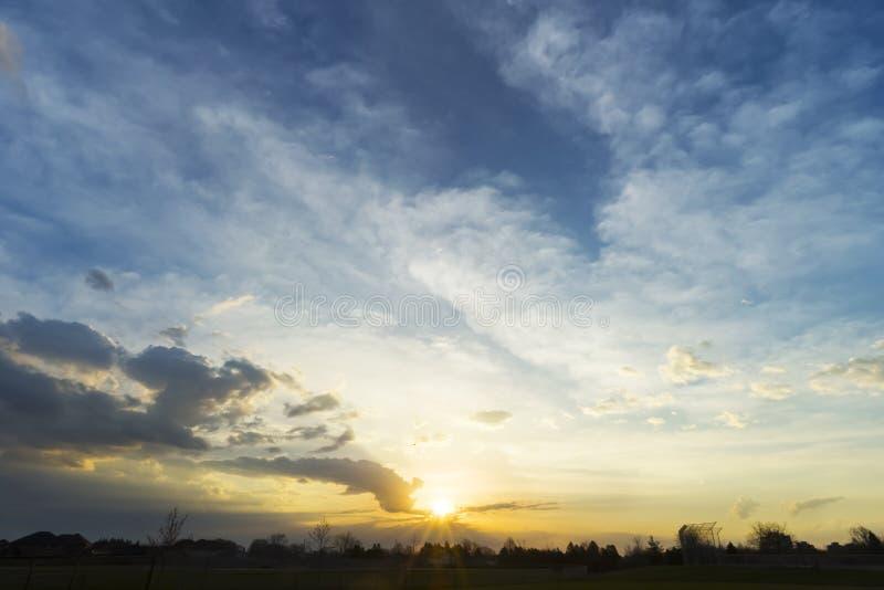 Nascer do sol dourado e céu azul sobre a silhueta do commu residencial fotos de stock