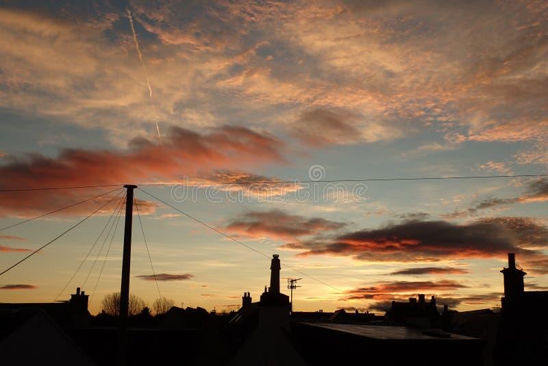 Nascer do sol dramático sobre telhados imagens de stock