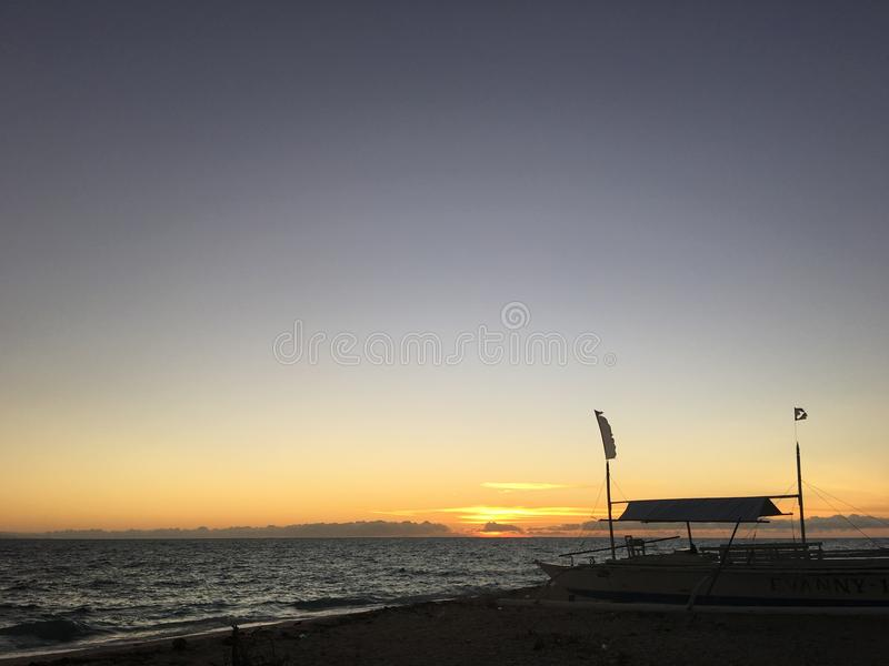 Nascer do sol e barco do catamarã na praia foto de stock
