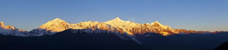 Nascer do sol em montanhas da neve em China fotos de stock