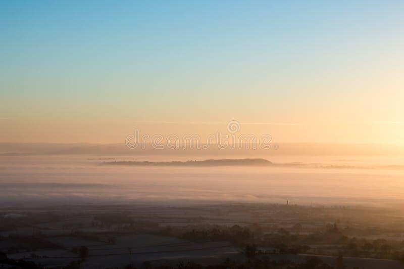 Nascer do sol em uma manhã gelado, enevoada bonita Vista para baixo em camadas de névoa através do countrysid de Engliseh imagens de stock