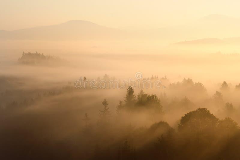 Nascer do sol em uma república checa Raias douradas A manhã nevoenta gosta de um fundo Montanhas pequenas e suas sombras fotografia de stock royalty free
