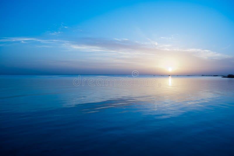 Nascer do sol do inverno no Mar Vermelho Céu azul e água calma no tempo do nascer do sol A manhã fria do sol O sol sob a água azu fotos de stock royalty free