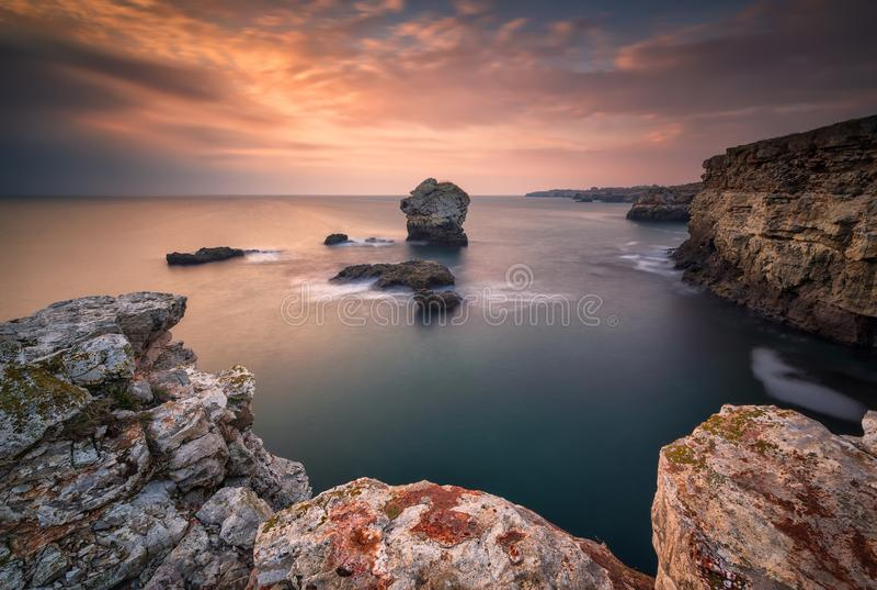 Nascer do sol do mar na praia rochosa foto de stock
