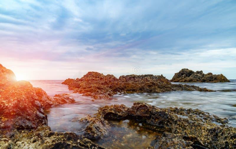 Nascer do sol na costa de mar rochosa fotos de stock