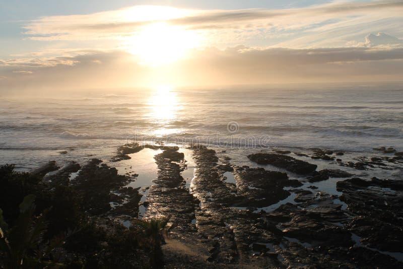 Nascer do sol na maré baixa na baía Londres do leste de Morgan na costa selvagem de África do Sul imagens de stock
