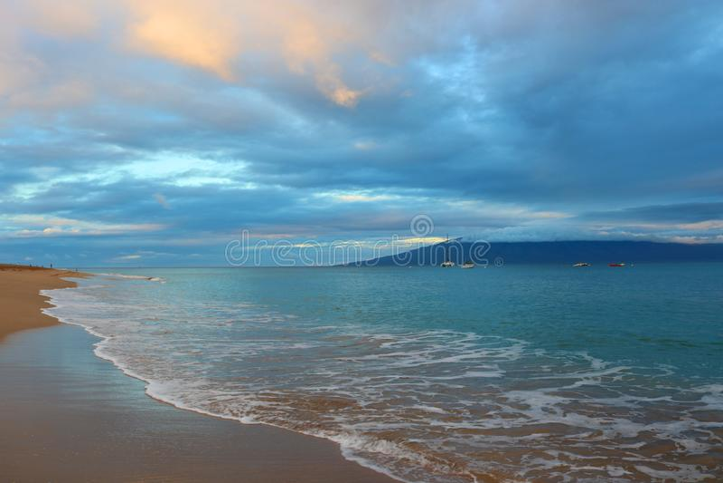 Nascer do sol na praia com rosa nebuloso e Gray Sky e água azul imagem de stock