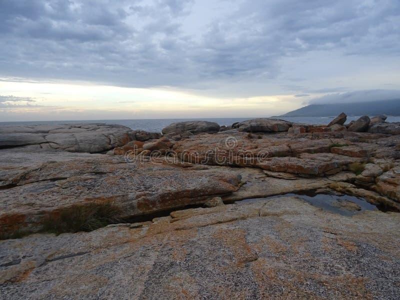 Nascer do sol na praia da rocha em Tasmânia foto de stock