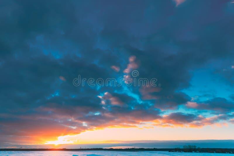 Nascer do sol natural do por do sol sobre o campo ou o prado Luz do sol de Sun no céu colorido sobre a terra nevado do inverno pa fotografia de stock