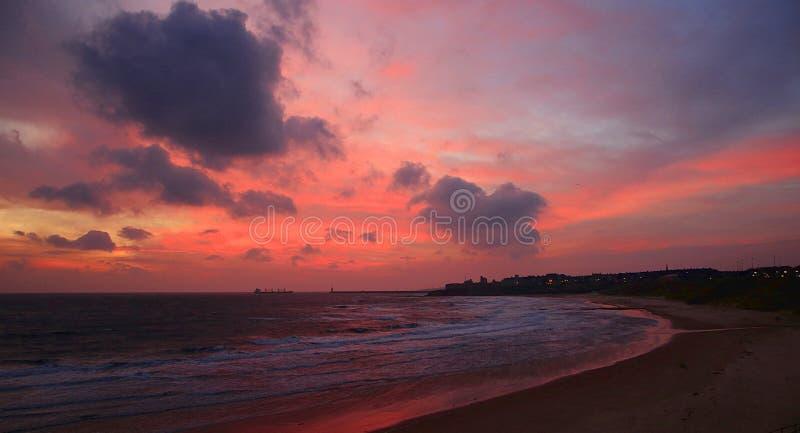 Nascer do sol nebuloso, cor-de-rosa na praia de Tynemouth Longsands imagem de stock royalty free
