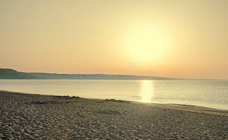 Nascer do sol no beira-mar, na areia e na água clara, a costa do Mar Negro foto de stock royalty free