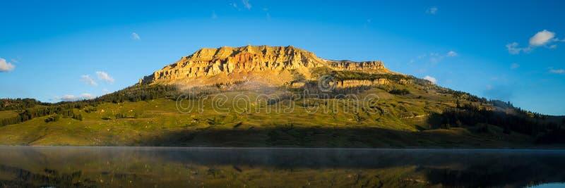 Nascer do sol no lago com o urso ao montículo no fundo, Montana fotos de stock royalty free