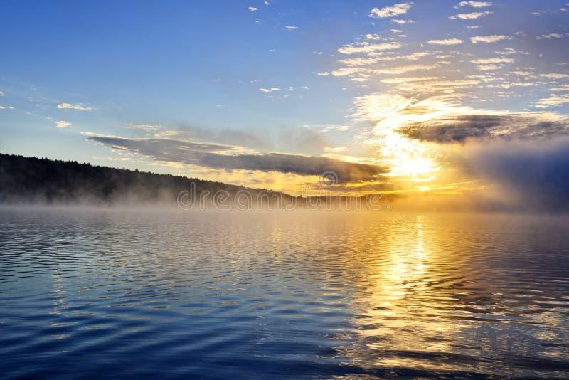 Nascer do sol no lago nevoento imagens de stock