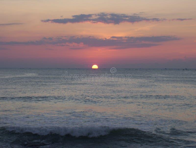 Nascer do sol no mar com o céu e as nuvens alaranjados da cor fotos de stock