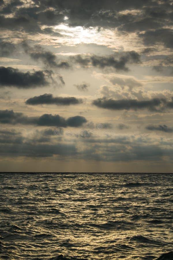 Nascer do sol no mar, com um céu dramático completamente de nuvens pretas Um dia de verão tormentoso foto de stock