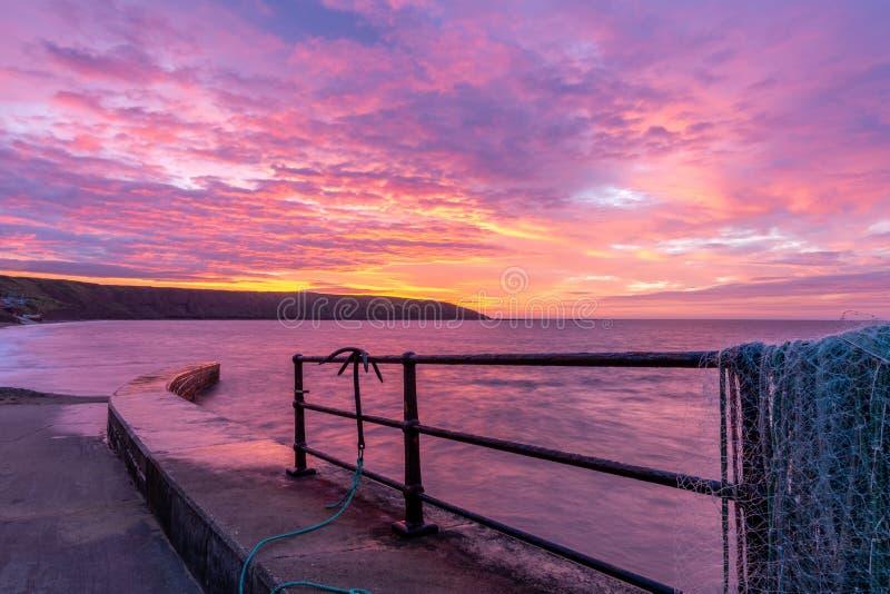 Nascer do sol no molhe da pesca de Filey que olha para Filey Brigg, Yorkshire, Reino Unido imagem de stock