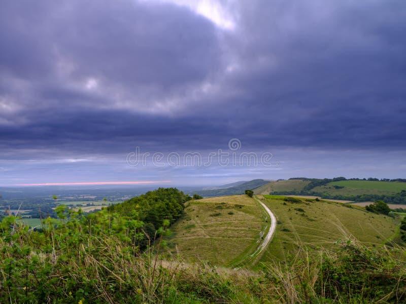 Nascer do sol nublado nebuloso do verão sobre o passeio sul da maneira das penas de Beacon Hill e de Harting para baixo nas penas fotografia de stock