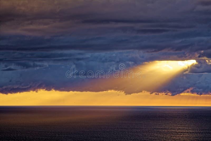 Nascer do sol por nuvens escuras sobre o oceano com raio de sol fotografia de stock