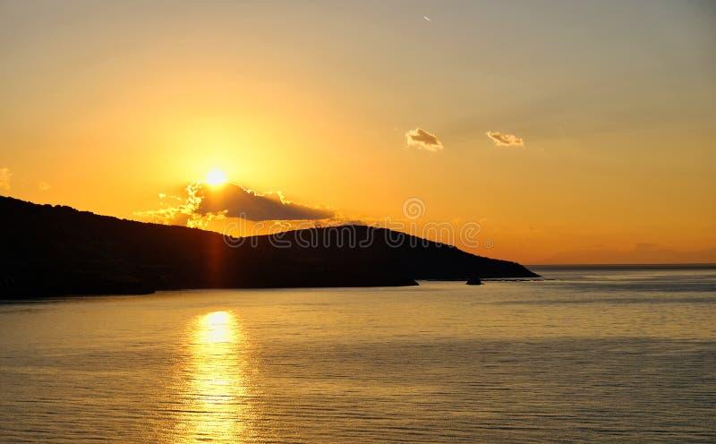 Nascer do sol que brilha através das nuvens e refletido na água do mar, Grécia fotos de stock