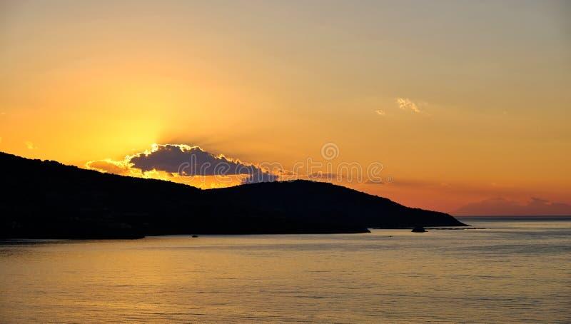 Nascer do sol que brilha através das nuvens e refletido na água do mar, Grécia foto de stock
