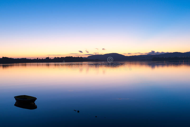 Nascer do sol sobre as transições do céu azul da baía a cor-de-rosa e a alaranjado de cima do horizonte e sobre a água calma fotos de stock royalty free
