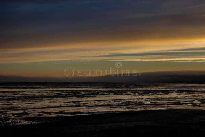 Nascer do sol sobre Bristol Bay da doca em Ekuk Alaska na maré baixa foto de stock royalty free