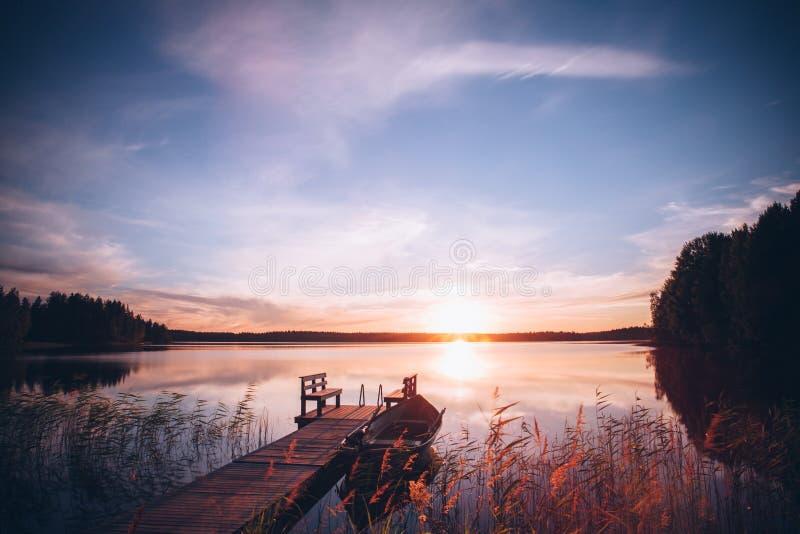 Nascer do sol sobre o cais da pesca no lago em Finlandia imagem de stock