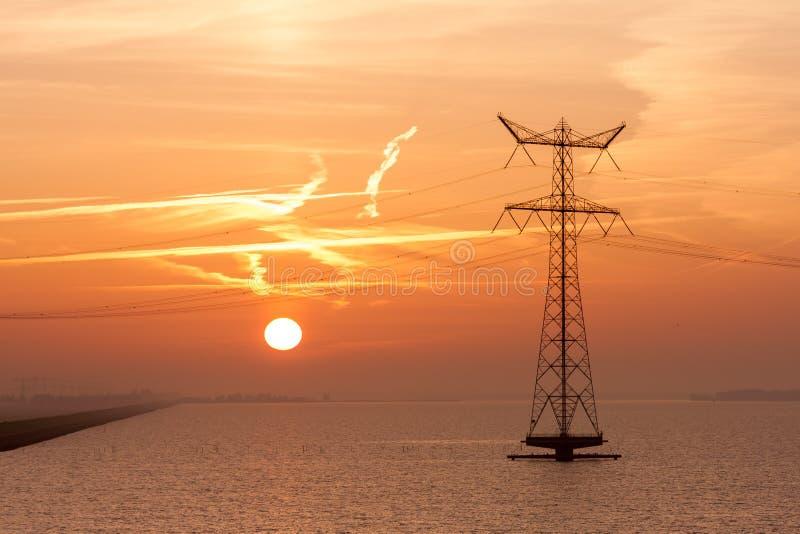 Nascer do sol sobre o mar com um pilão da eletricidade imagens de stock