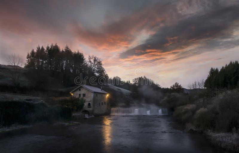 Nascer do sol sobre o moinho de água fotos de stock