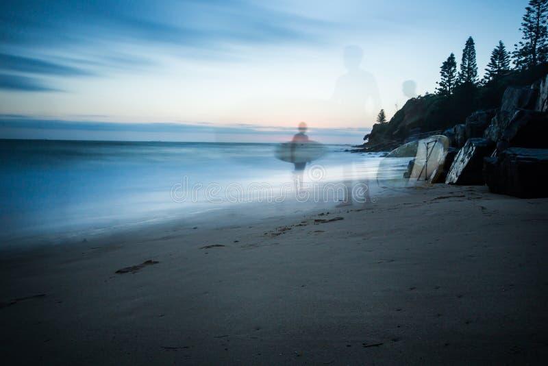 Nascer do sol sobre o oceano e a silhueta dos surfistas imagem de stock