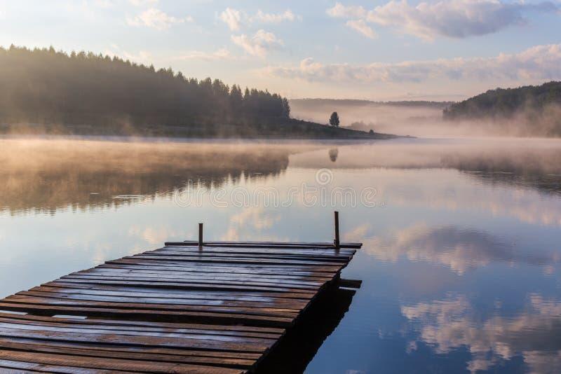 Nascer do sol sobre o rio nevoento com um cais de madeira fotos de stock royalty free