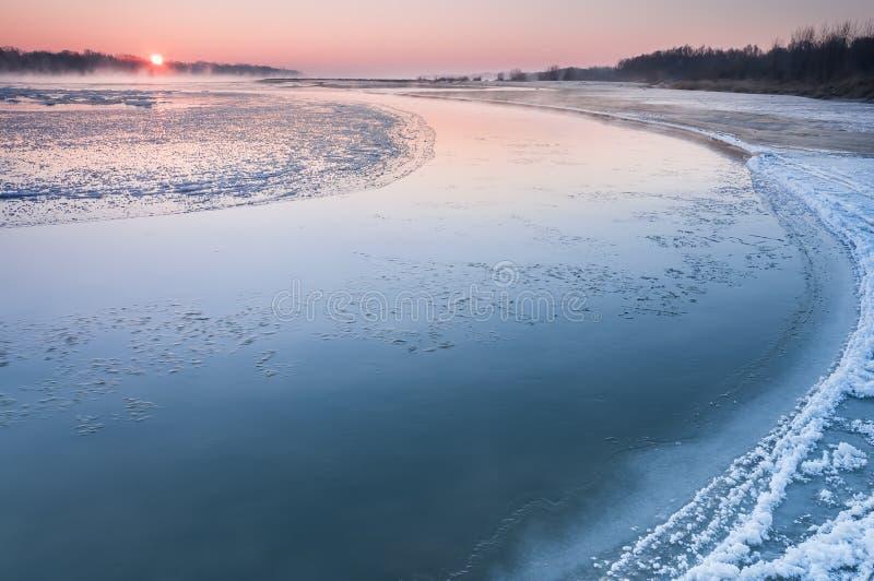 Nascer do sol sobre um rio de congelação coberto na névoa imagem de stock