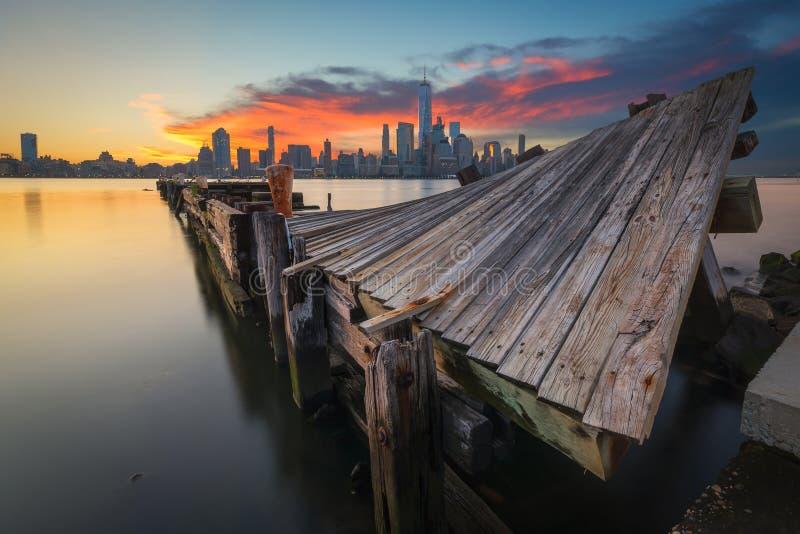 Nascer do sol torcido do cais com o Manhattan no fundo fotos de stock