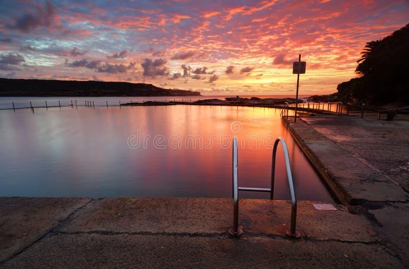 Nascer do sol vermelho do verão sobre a baía longa da associação da rocha do oceano de Malabar Austral foto de stock