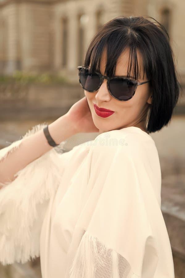 Nasconda la sua emozione dietro gli occhiali da sole L'acconciatura castana del peso della ragazza sembra alla moda Signora alla  fotografia stock libera da diritti
