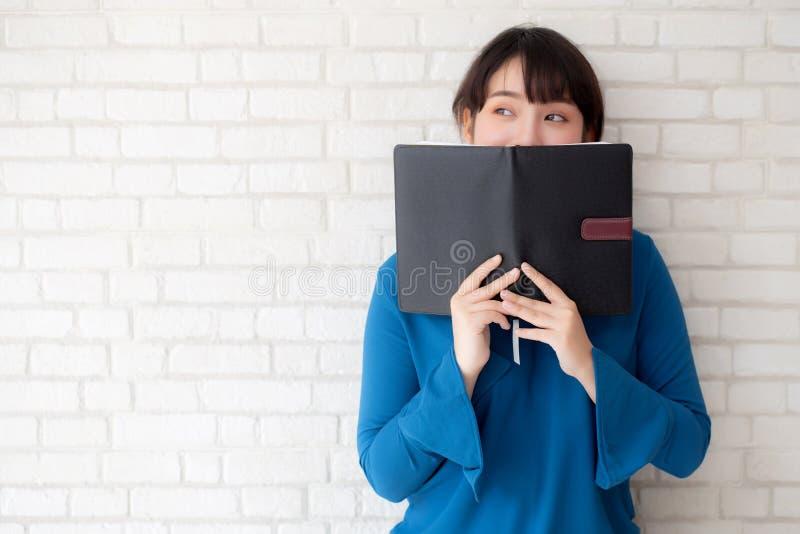 Nascondersi felice della bella donna asiatica del ritratto giovane dietro la copertura del libro di fondo concreto del mattone o  fotografia stock libera da diritti