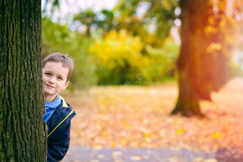 Nascondersi sorridente felice dietro l'albero fotografie stock