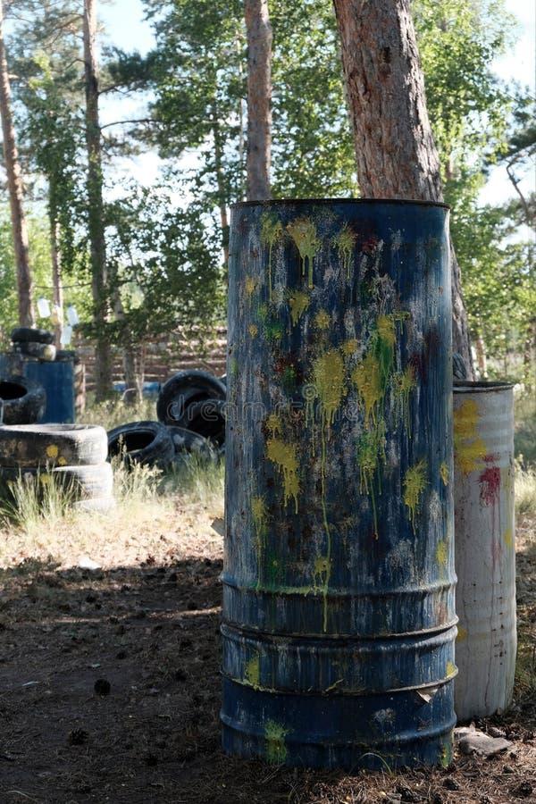 Nascondiglio di paintball Barilotto con le macchie dei colori differenti nella foresta il territorio per un gioco di squadra dell fotografia stock
