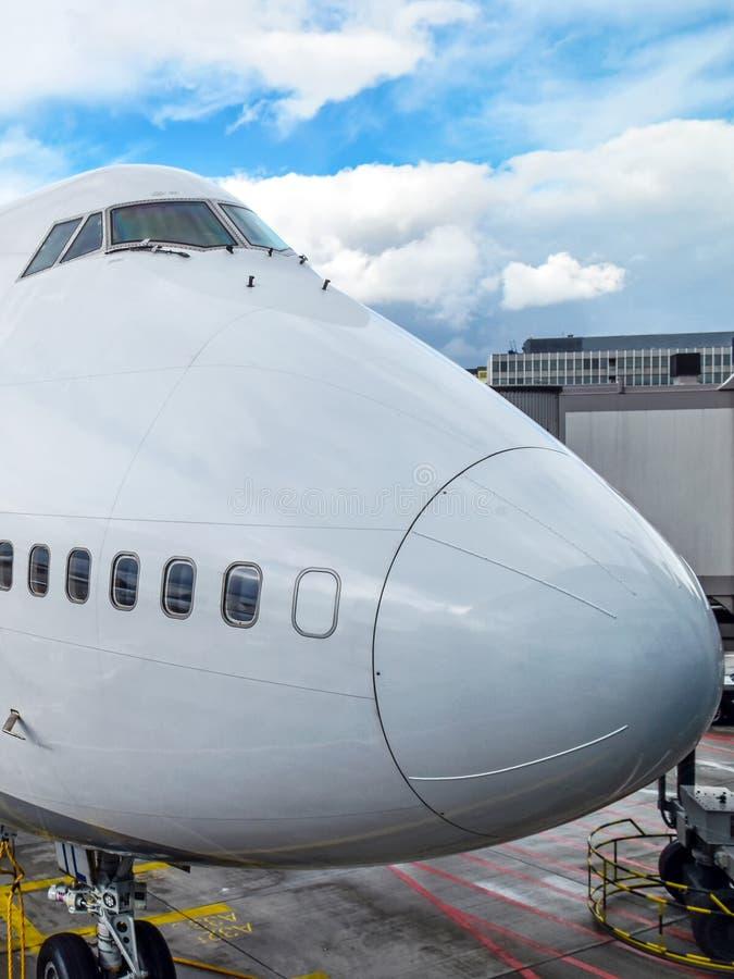 Nase eines großen weißen Flugzeuges an einem Flughafen stockbild