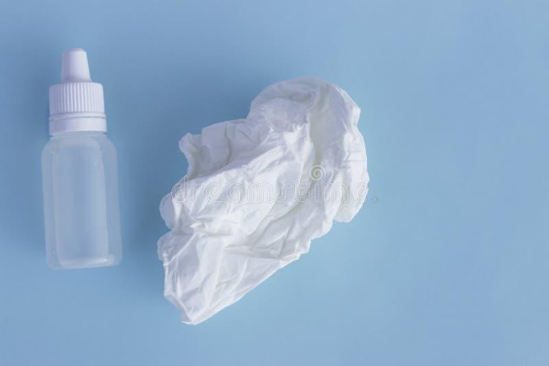 Nasentropfen und zerknittertes Gewebe auf einem blauen Hintergrund, das Konzept von Kälten, Infektion, Rhinitis stockbilder